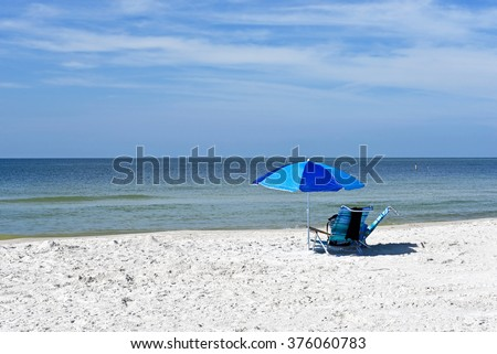 Beach Umbrella and Two Chairs on the Beach with the ocean and sky in the background - stock photo