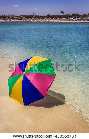 Beach umbrella on a sunny day, sea in background - stock photo