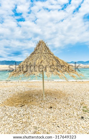 Beach umbrella on a windy day on the coast of tropical island - stock photo