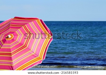 beach umbrella on the beach and the blue sea - stock photo