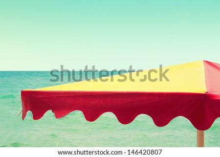 beach umbrella on the sea background, vintage retro style - stock photo