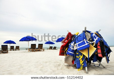 Beach umbrellas, chairs, and life jackets on deserted beach. - stock photo
