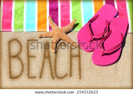 Beach vacation concept - word written on golden sand with a starfish, pink flip flops and towel conceptual of a summer vacation and travel to a sunny destination for a relaxing suntan. - stock photo