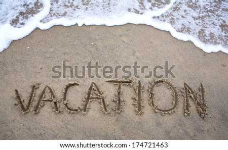 Beach Vacation concept written in sand as ocean waves approach. - stock photo
