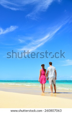 Beach vacation couple relaxing on summer holidays. Young people standing from behind holding hands looking at the ocean, vertical crop with a lot of copy-space in the blue sky. Travel concept. - stock photo