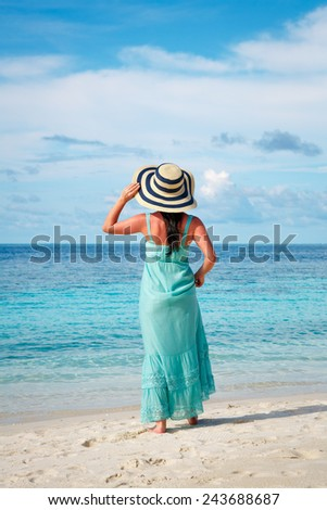 Beach vacation. Girl walking along a tropical beach in the Maldives. - stock photo