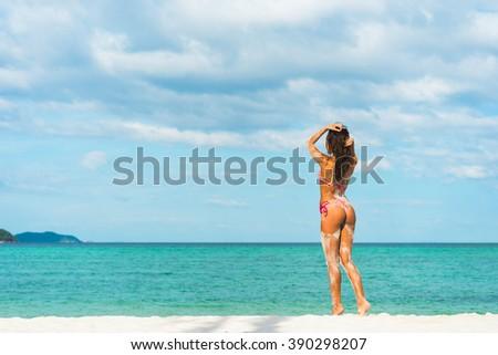 Beach vacation. Hot beautiful woman in bikini standing and  enjoying looking view of beach ocean on hot summer day.  - stock photo