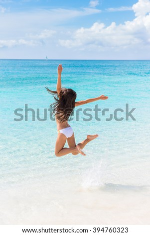 Beach vacation success woman jumping of joy and happiness cheering winning splashing water in ocean. Winner girl from behind with arms up in the air cheerful enjoying summer vacations travel. - stock photo