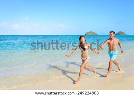 Beach vacations - happy couple running together joyful in water during holidays in Hawaii. - stock photo