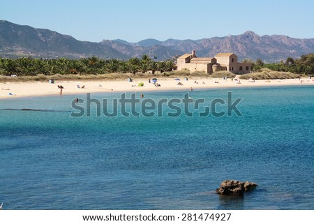 beach view with traditional rock house. Sand beach and blues sea. Mountains afar. Rocks in water.  By the sea in Sardegna. Sardinia. Italy - stock photo