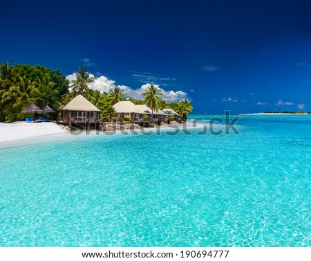 Beach Villas on small tropical island with palm trees - stock photo