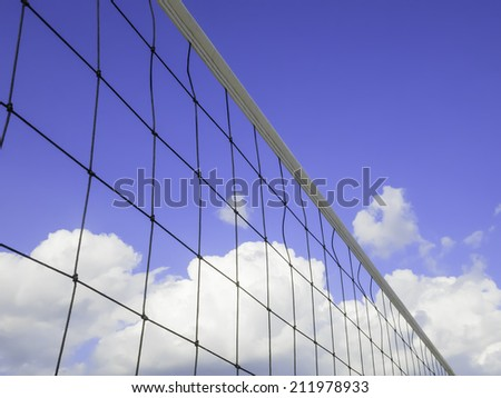 Beach volleyball net with blue sky, summer clouds, and copy space - stock photo