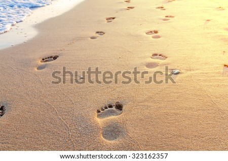 Beach, wave and footsteps in Greece, yellow sun - stock photo