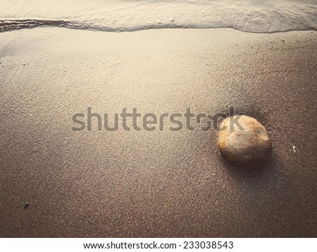 Beach waves and rocky beach with sunset - stock photo