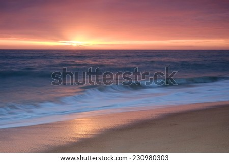 Beach waves onto the shore during late afternoon - stock photo