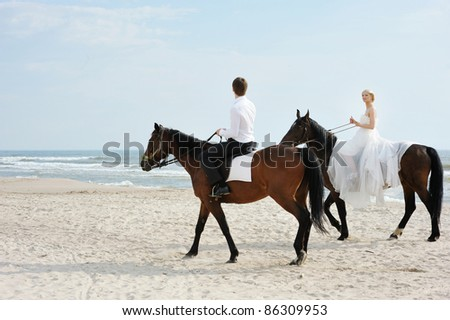 Beach wedding: bride and groom on a horses by the sea - stock photo