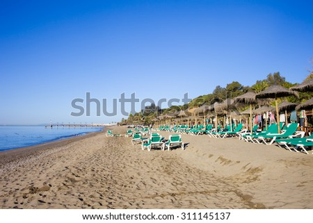 Beach witch sun loungers in Marbella, Spain, Costa del Sol, Andalucia region. - stock photo