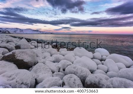 Beach with big round stones on the coast of the Barents Sea, Arctic - stock photo