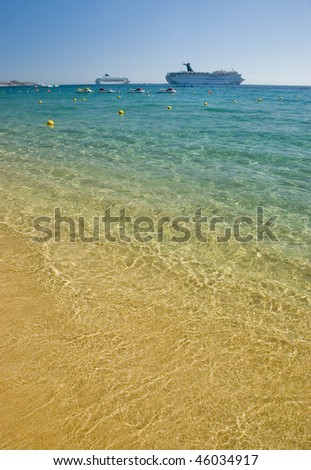 Beach with crystal clear water. Cabo San Lucas, Mexico. Two cruise ships can be seen in the background - stock photo