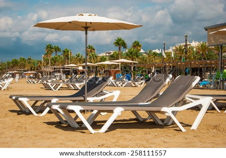 Beach with deckchairs and umbrellas in Salou in Spain - stock photo