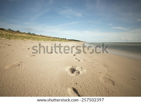 Beach with footprints in the sand, photographed with long exposure - stock photo