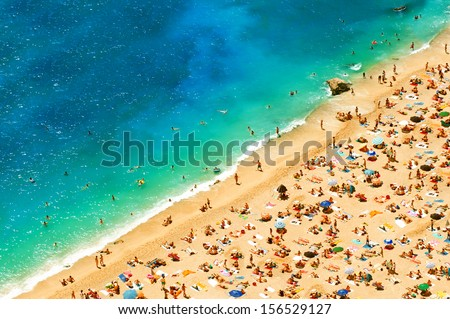 beach with tourists, sunbeds and umbrellas. travel background. top view - stock photo
