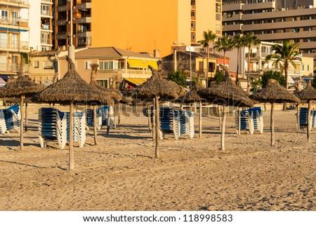 Beach with umbrellas and benches on Mallorca - stock photo
