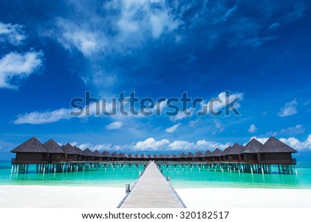 beach with water bungalows at Maldives - stock photo