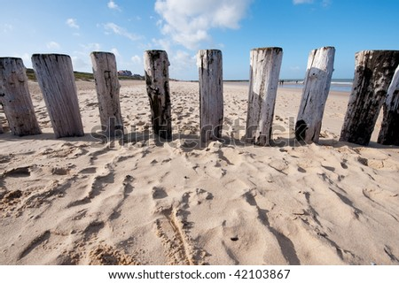Beach with wooden weave breakers in landscape - stock photo