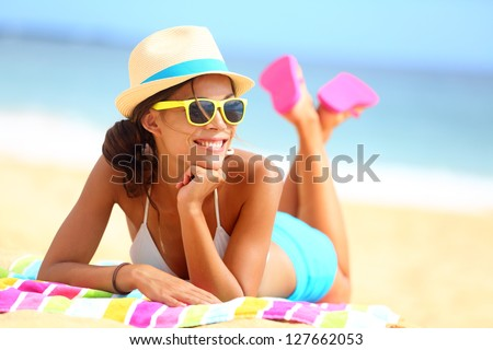 Beach woman funky happy and colorful wearing sunglasses and beach hat having summer fun during travel holidays vacation. Young multiracial trendy cool hipster woman in bikini lying in the sand. - stock photo