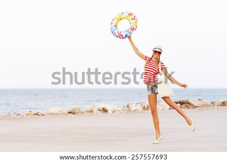 Beach woman happy and colorful wearing sunglasses and beach hat having summer fun during travel holidays vacation. - stock photo
