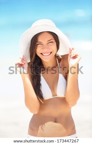 Beach woman happy and playful smiling laughing playful and cheerful in summer sun. Beautiful multiracial Asian Chinese / Caucasian woman wearing white beach hat and bikini. - stock photo