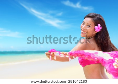 Beach woman in bikini happy on vacation paradise beach waving scarf sarong in wind happy in on travel holiday in tropical Hawaii an beach. Beautiful biracial Asian Caucasian girl. - stock photo