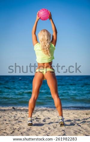 Beach woman in bikini holding a volleyball - stock photo