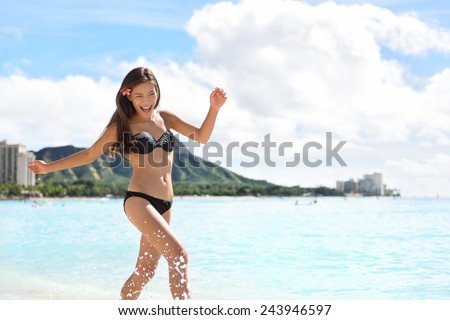 Beach woman in bikini on Waikiki, Oahu, Hawaii, USA. Girl on travel vacation holidays running having fun splashing water on Hawaiian Waikiki beach with Diamond Head mountain. Asian Caucasian model. - stock photo