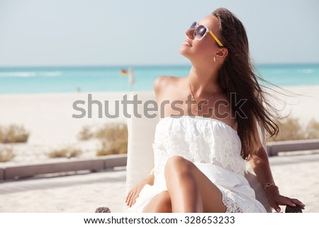 Beach woman in white dress enjoying the summer sun happy sitting in a sunbed at the tropica beach with face raised to the sunlight.  - stock photo