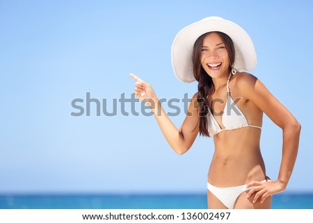 Beach woman pointing showing vacation concept. Beautiful happy summer bikini girl on tropical beach holidays travel pointing happy smiling at copy space. Attractive multiracial Asian Caucasian model. - stock photo