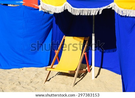 Beach wooden chaise lounge and umbrella with fringe. Trouville-sur-Mer (Normandy, France). Selected focus on umbrella.  - stock photo