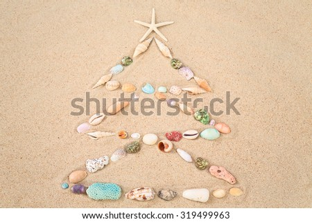 Beach Xmas concept on sand as a Christmas tree with shells - stock photo