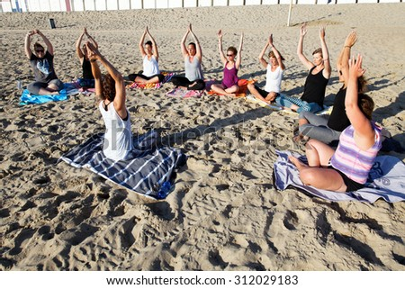 beach yoga group in the sand - stock photo