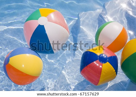 Beachballs in a bright blue pool - stock photo