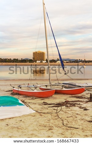 Beached catamaran. Late afternoon, golden hour colors. 2 hull sailboat on the sand. Rolled up sail. Calm, still water in the bay. Building reflection in background. Cloudy sky. Vertical scene. - stock photo