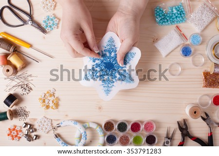 Beaded snowflakes for Christmas tree. Preparation for handmade, top view on the table - stock photo