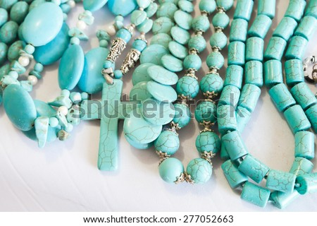 Beads of blue turquoise stone lie on the counter of souvenir shop on the beach in Dominican republic - stock photo