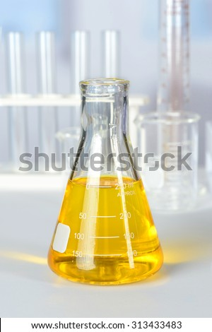 Beaker with yellow colorant on laboratory table - stock photo