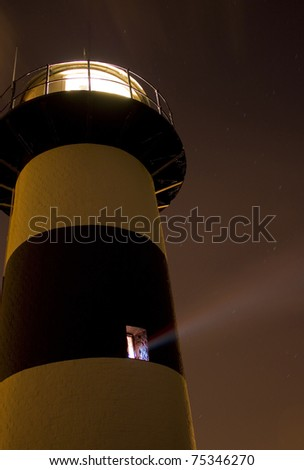 Beam of light from a Lighthouse a window in the lighthouse throws a beam of light out into the night - stock photo
