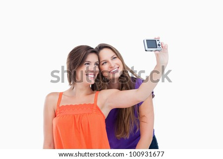 Beaming teenager taking a photo of herself and a smiling friend - stock photo