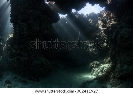 Beams of light descend into the shadows of a dim cavern in the Solomon Islands. Coral reefs in this Melanesian region are exceedingly diverse. The area also offers great scuba diving and snorkeling. - stock photo