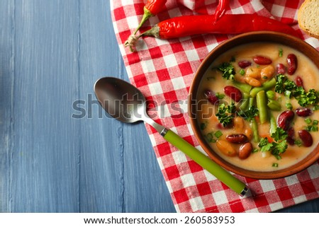 Bean soup in bowl with fresh sliced bread on napkin, on color wooden table background - stock photo
