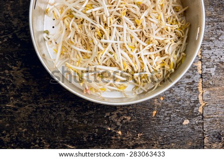 bean sprouts in old colander on dark wooden background, top view, close up - stock photo